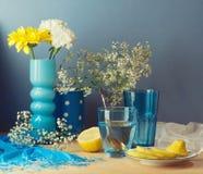 Ainda vida com água, o limão e as flores na tabela de madeira Imagens de Stock