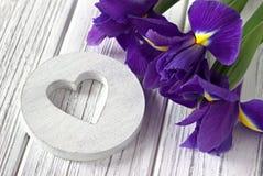 Ainda a vida com a íris do sinal do coração floresce no fundo de madeira branco casamento Fotografia de Stock Royalty Free