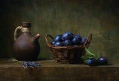 Ainda vida com ameixas em uma cesta na tabela Fotos de Stock Royalty Free