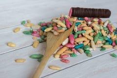 Ainda vida com arroz doce com esmalte do açúcar e doces de chocolate no fundo de madeira Imagem de Stock Royalty Free