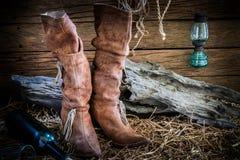 Ainda vida com as botas de couro tradicionais no fundo do celeiro Imagens de Stock Royalty Free
