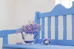 Ainda vida com as flores da mola no banco Imagens de Stock Royalty Free