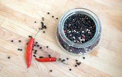 Ainda vida com as sementes da pimenta vermelha da paprika e da pimenta preta dentro do frasco de vidro redondo e dispersadas no f Imagem de Stock Royalty Free
