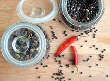Ainda vida com as sementes da pimenta vermelha da paprika e da pimenta preta dentro do frasco de vidro redondo e dispersadas no f Fotos de Stock Royalty Free