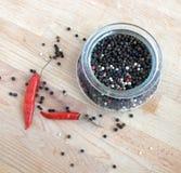 Ainda vida com as sementes da pimenta vermelha da paprika e da pimenta preta dentro do frasco de vidro redondo e dispersadas no f Foto de Stock