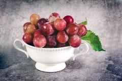 Ainda vida com as uvas vermelhas no copo branco do vintage Fotografia de Stock Royalty Free