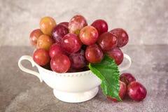 Ainda vida com as uvas vermelhas no copo branco do vintage, foc seletivo Fotografia de Stock