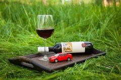 Ainda vida com bandeja, pouco carro vermelho, garrafa, vidro do outd do vinho Fotos de Stock Royalty Free