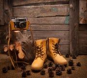 Ainda vida com botas e a câmera retro em de madeira Fotos de Stock Royalty Free