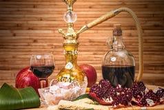 Ainda-vida com cachimbo de água, vinho, grandada e doces Fotos de Stock