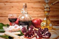 Ainda-vida com cachimbo de água, vinho, grandada e doces Fotografia de Stock