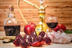 Ainda-vida com cachimbo de água, vinho, grandada e doces Fotografia de Stock Royalty Free