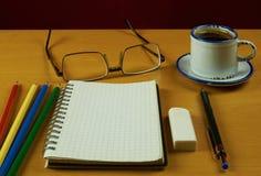 Ainda vida com caderno, xícara de café, vidros, pena e colore Imagens de Stock Royalty Free