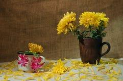 Ainda vida com canecas e flores da argila na toalha de mesa Fotografia de Stock