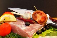 Ainda vida com carne, tomate e faca na placa de corte Foto de Stock Royalty Free