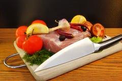 Ainda vida com carne, tomate e faca na placa de corte Fotos de Stock Royalty Free