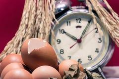 Ainda vida com cascas de ovo e ovos, despertador quebrado velho, padd Fotos de Stock