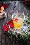 Ainda vida com chá do viburnum no guardanapo do pano de saco, no fundo de madeira Fotos de Stock