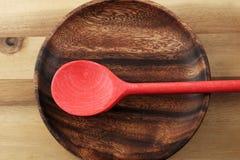 Ainda vida com a colher, a placa e placa de madeira vermelhas Foto de Stock Royalty Free