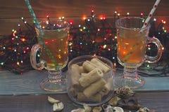 Ainda vida com copos de chá, uma bacia de cookies e luzes feericamente Fotografia de Stock Royalty Free