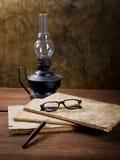 Ainda-vida com escrita-livros velhos e uma lâmpada Imagem de Stock