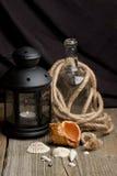 Ainda-vida com escudos velhos da lanterna, do frasco e do mar Imagens de Stock