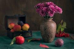 Ainda vida com flores do outono Os crisântemos em um vaso em uma toalha de mesa verde são decorados com maçãs e ameixa do outono Imagens de Stock Royalty Free