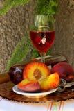 Ainda vida com garrafa, vidro do vinho e pêssegos Fotos de Stock Royalty Free