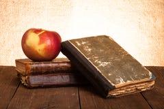 Ainda vida com maçã e uma pilha de livros velhos na aba de madeira velha Imagens de Stock