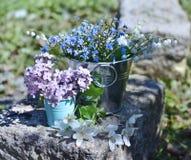 Ainda a vida com miosótis e lilás floresce nas cubetas na pedra Fotos de Stock