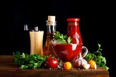 Ainda vida com molho dos tomates, da salsa, do alho, do azeite e de tomate em placas de madeira Em um fundo preto Fotografia de Stock Royalty Free
