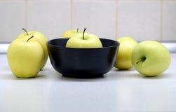 Ainda vida com muitas maçãs amarelas maduras na cozinha na opinião dianteira da tabela e da bacia Imagem de Stock