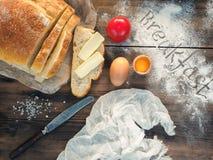 Ainda vida com o café da manhã da palavra na farinha Tabela de madeira com faca, pano, e refeições, vista superior Pão cortado co Foto de Stock