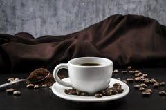 Ainda vida com o copo branco com café e os feijões de café deliciosos Imagens de Stock