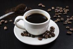 Ainda vida com o copo branco com café e os feijões de café deliciosos Fotos de Stock