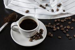 Ainda vida com o copo branco com café e os feijões de café deliciosos Fotos de Stock Royalty Free