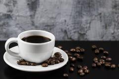Ainda vida com o copo branco com café e os feijões de café deliciosos Foto de Stock