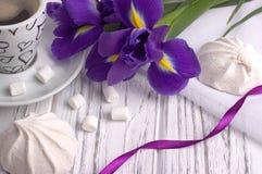 Ainda a vida com o copo da íris do zéfiro do marshmallow do coffe floresce a fita roxa no fundo de madeira branco casamento Rosa  Imagens de Stock Royalty Free