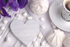 Ainda a vida com o copo da íris do zéfiro do marshmallow do coffe floresce o sinal do coração no fundo de madeira branco Imagens de Stock