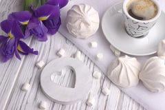 Ainda a vida com o copo da íris do zéfiro do marshmallow do coffe floresce o sinal do coração no fundo de madeira branco Foto de Stock