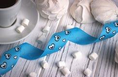 Ainda a vida com o copo da íris do zéfiro do marshmallow do coffe floresce o sinal do coração no fundo de madeira branco casament Imagem de Stock Royalty Free