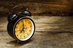 Ainda vida com o despertador na tabela de madeira Fotografia de Stock Royalty Free