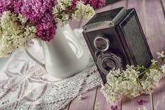 Ainda vida com o lilás roxo e branco no vaso branco com a câmera do vintage na tabela cor-de-rosa, planta de florescência da mola Fotos de Stock Royalty Free