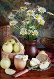 Ainda vida com o ramalhete da camomila em um vaso e em maçãs Fotos de Stock