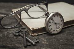 Ainda vida com o relógio de bolso velho, livro chaves e vidros na tabela de madeira Fotos de Stock