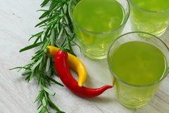 Ainda vida com os cocktail verde-claro no fundo, na pimenta e em alecrins de madeira próximo Imagem de Stock