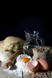 Ainda vida com os ingredientes para fazer o pão na tabela de madeira sobre o fundo preto Imagem de Stock Royalty Free