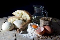 Ainda vida com os ingredientes para fazer o pão na tabela de madeira sobre o fundo preto Imagem de Stock