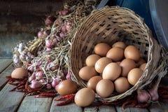 Ainda vida com os ovos na cesta, nas cebolas, nos alho e na pimenta de bambu Imagem de Stock Royalty Free