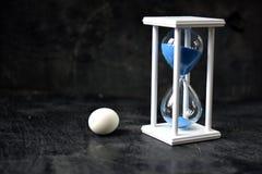 Ainda-vida com ovo branco e sandglass no fundo preto Imagens de Stock Royalty Free